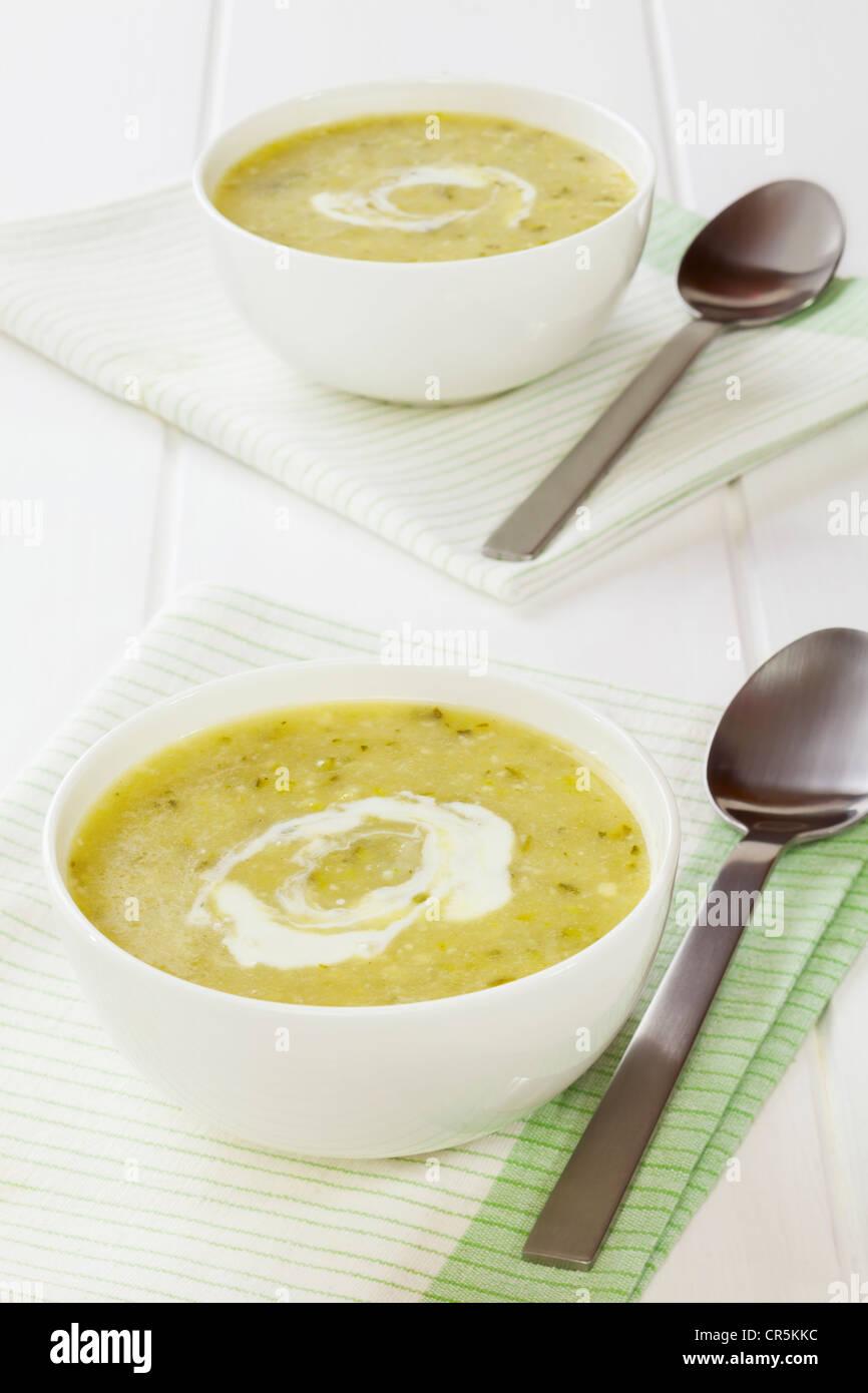 Due ciotole di zucchine o zuppa di zucca, roteato con crema. Immagini Stock