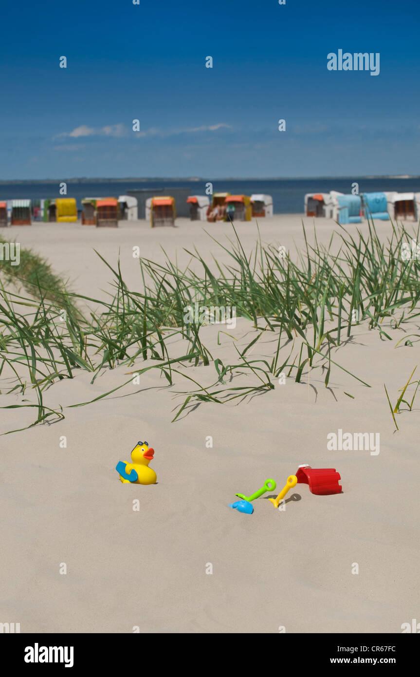 Colorato i giocattoli per bambini, benna, vanghe e anatra, nella sabbia sulla spiaggia di Norden, sdraio in spiaggia Immagini Stock