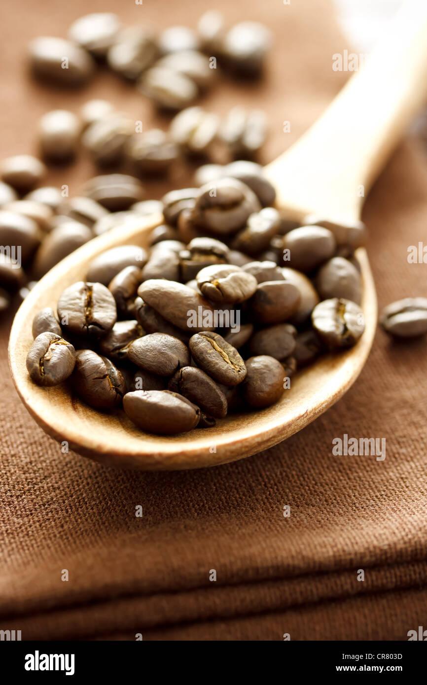 I chicchi di caffè in cucchiaio di legno sul panno marrone Immagini Stock
