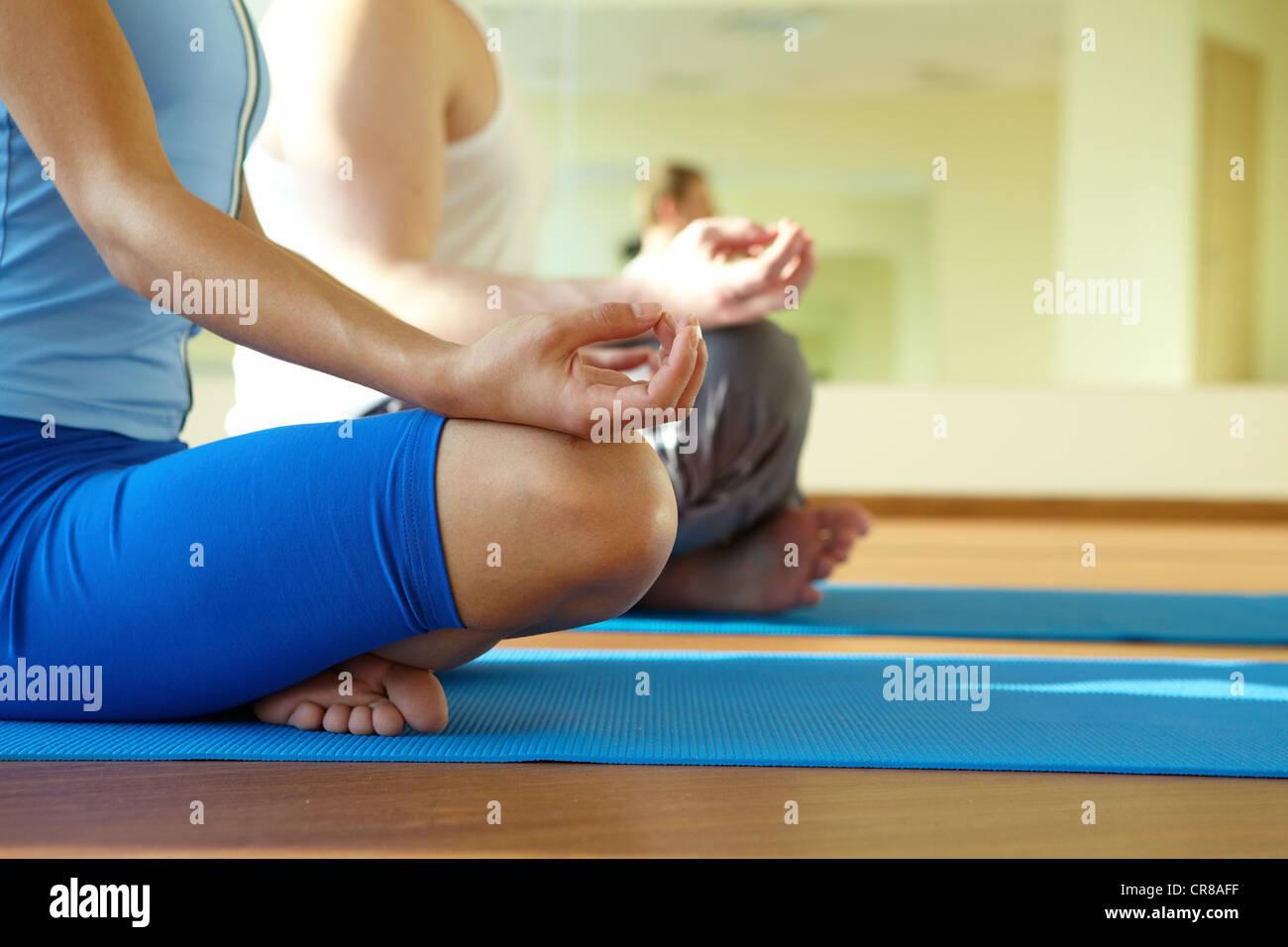 Close-up di femminile e maschile braccia e gambe incrociate durante la meditazione Immagini Stock