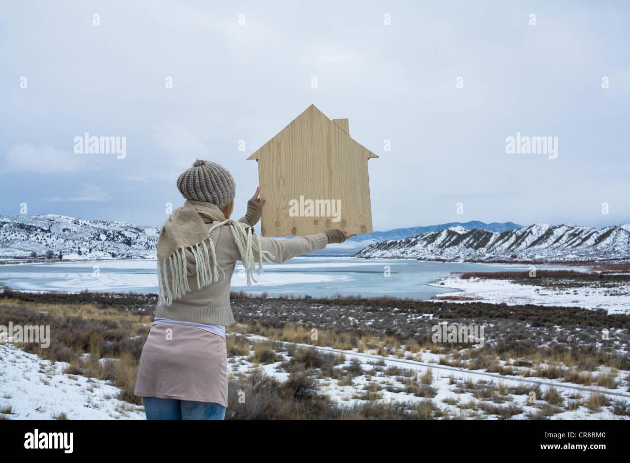 La donna nel paesaggio panoramico con sagoma in legno di una casa Immagini Stock