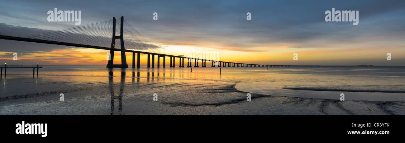Immagine di panorama del ponte Vasco da Gama a Lisbona, Portogallo durante il tramonto con la riflessione nel fiume Tago Foto Stock