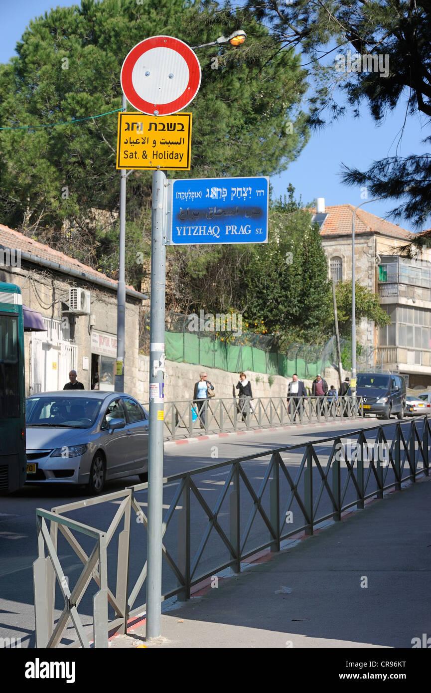 Il nome di una via a segno con il nome arabo spruzzata sopra, gli ebrei ortodossi nella parte posteriore, Gerusalemme, Immagini Stock