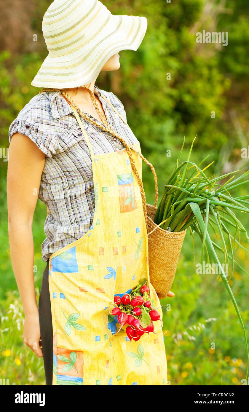 Donna felice giardiniere lavorando sul campo, giovane femmina cestello di contenimento, ragazza crescente verde Foto Stock