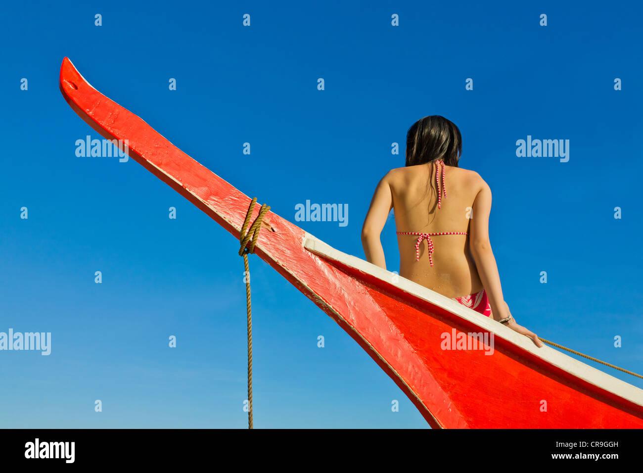 Donna seduta sul dipinto di rosso barca, Isola di Bohol, Filippine Foto Stock