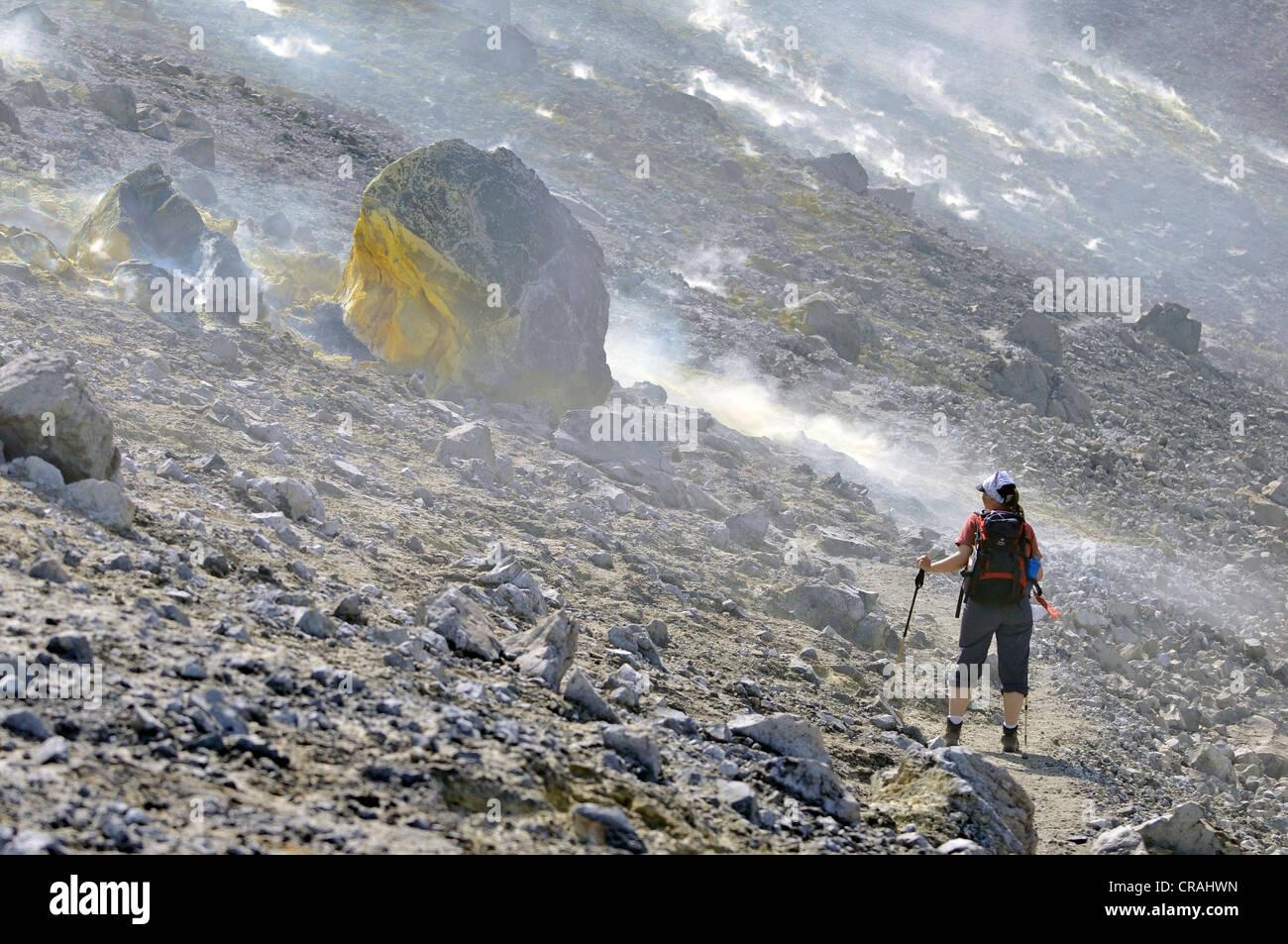 Escursionista trekking attraverso i fumi di zolfo e rocce vulcaniche, isola di Vulcano, Eolie o Lipari Isole, Sicilia, Immagini Stock