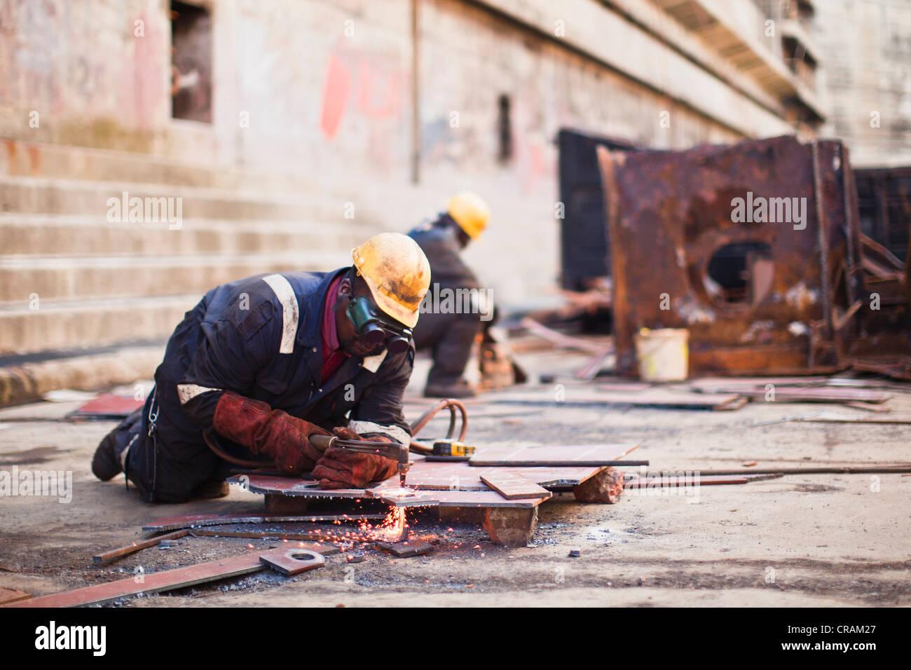 Saldatrici a lavoro sul bacino di carenaggio Immagini Stock