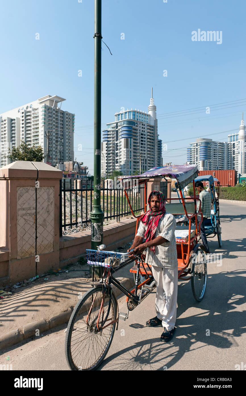 In rickshaw drivers di fronte a nuove zone residenziali alti edifici in Gurgaon, Haryana, India, Asia Immagini Stock