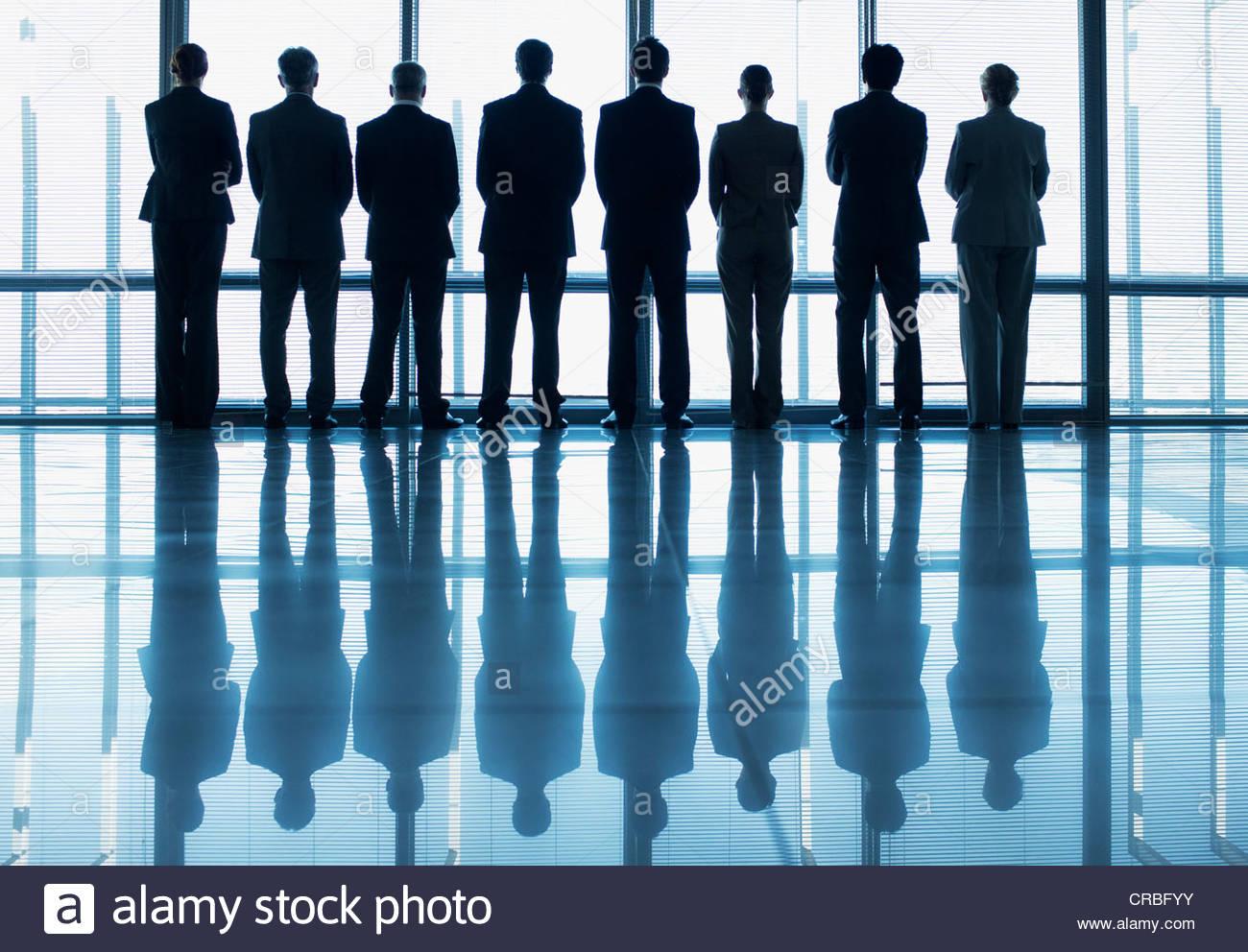 Silhouette di gente di affari in una fila a guardare fuori dalla finestra della lobby Immagini Stock
