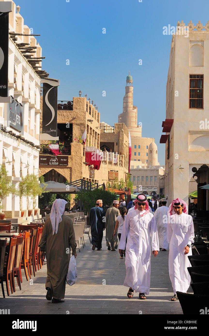 Pedoni nel Souq Waqif con la torre del Qatar centro culturale islamico, FANAR, Doha, Qatar, Medio Oriente Immagini Stock