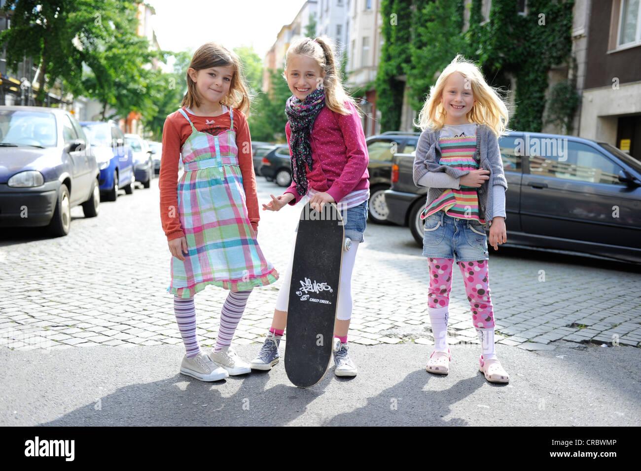 Tre ragazze con uno skateboard in una strada residenziale nel centro di Dusseldorf, Renania settentrionale-Vestfalia, Immagini Stock