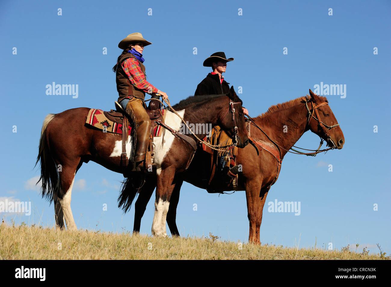 Cowgirl e cowboy su cavalli guardando in lontananza, Saskatchewan, Canada, America del Nord Foto Stock