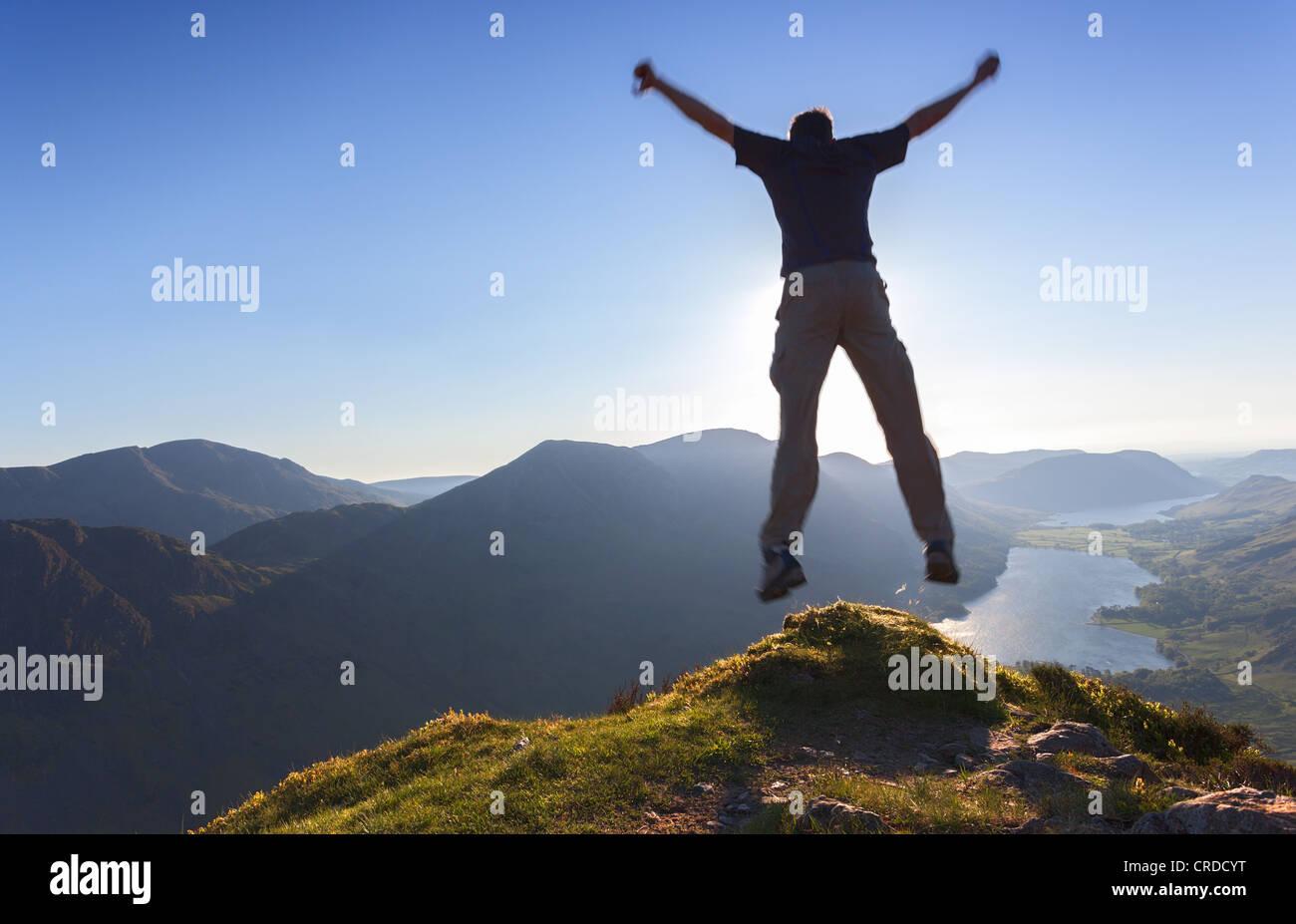 Un uomo salta fuori da un bordo di una montagna. Immagini Stock
