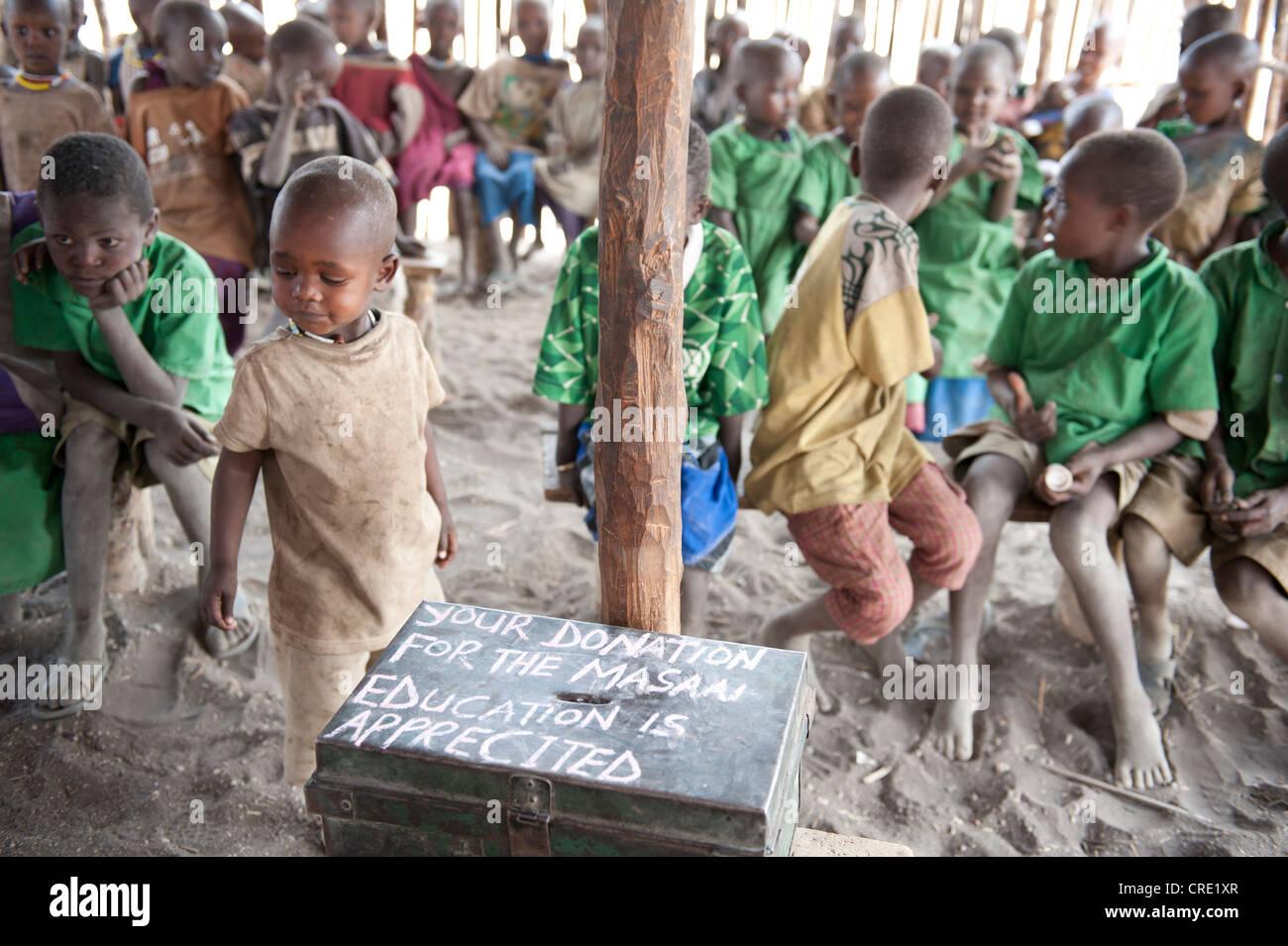 Istruzione e povertà, i bambini di una scuola primaria di classe con una donazione box, etnologia, Masai, villaggio Immagini Stock