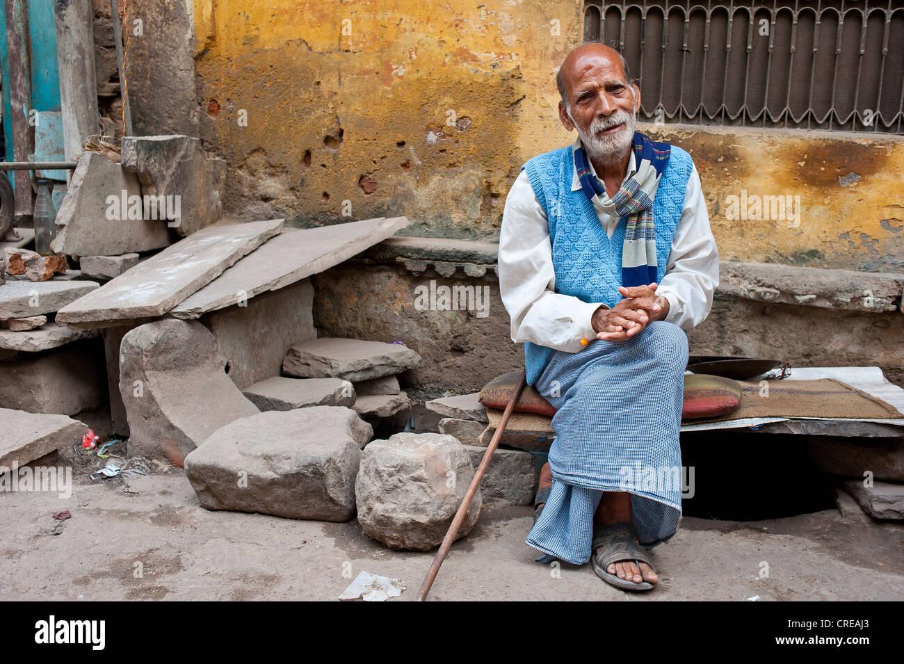 Anziani uomo indiano, del Rajasthan, seduta su una panchina in pietra con cuscini di fronte a una casa di riposo Immagini Stock