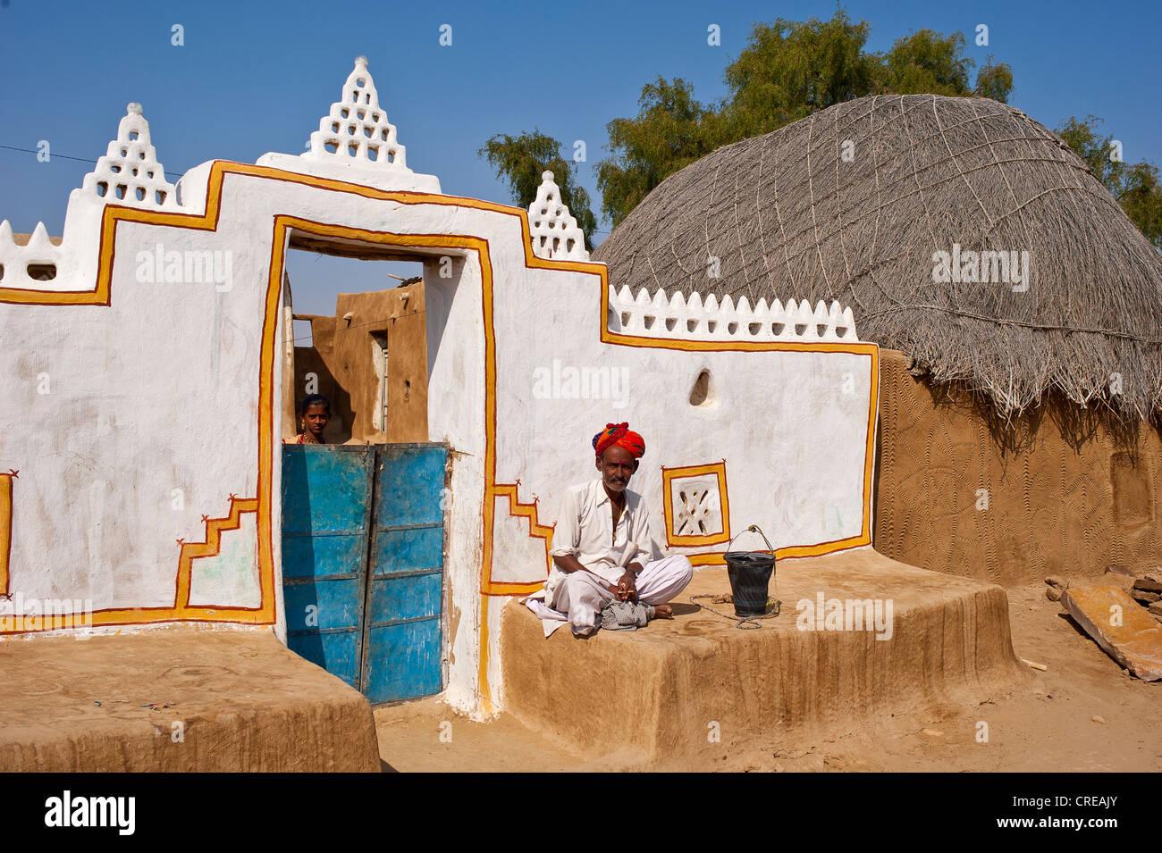 Rajasthani, Indiana uomo che indossa un dhoti e turbante, seduto di fronte al suo tradizionalmente costruito e dipinto Immagini Stock