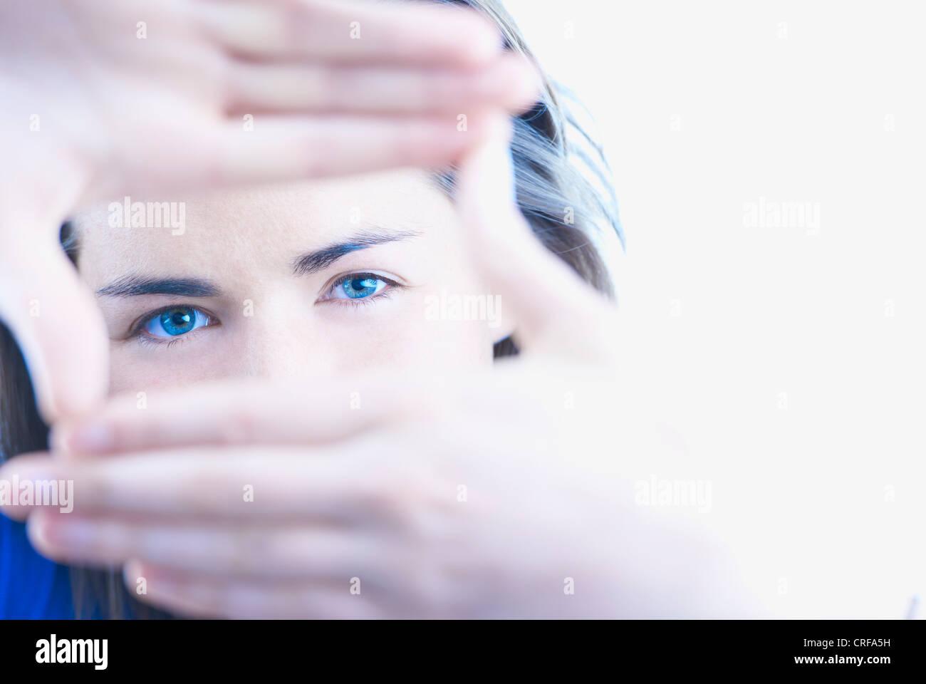 Donna che fa il mirino con le mani Immagini Stock