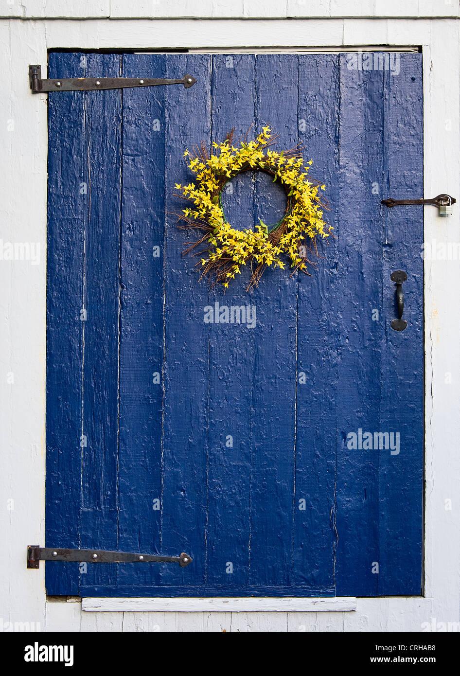 Semplice ghirlanda di fiori su rustiche porta blu. Immagini Stock