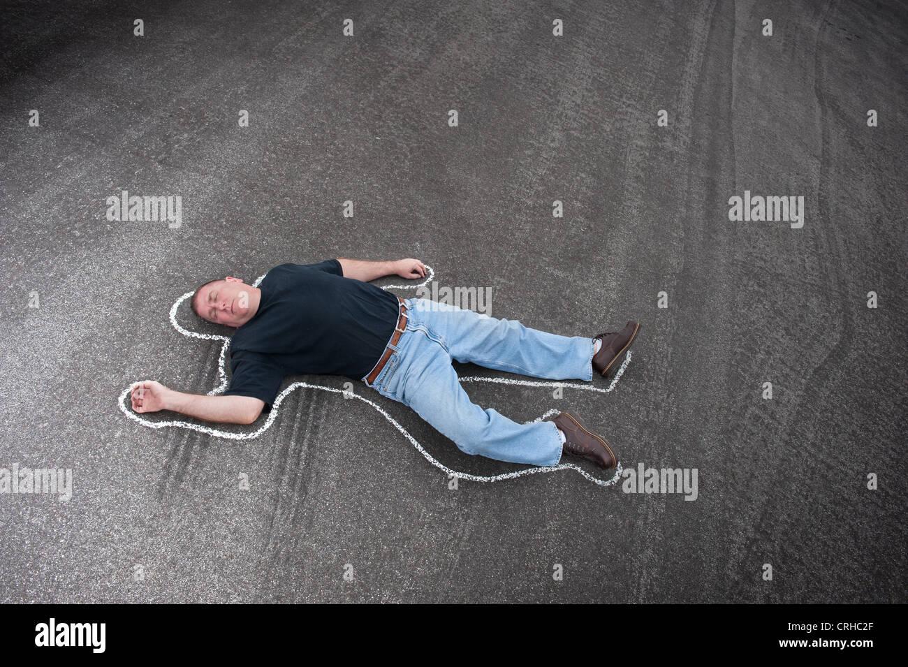 Un uomo morto in strada delineata con chalk dalla scena del crimine gli investigatori. Immagini Stock