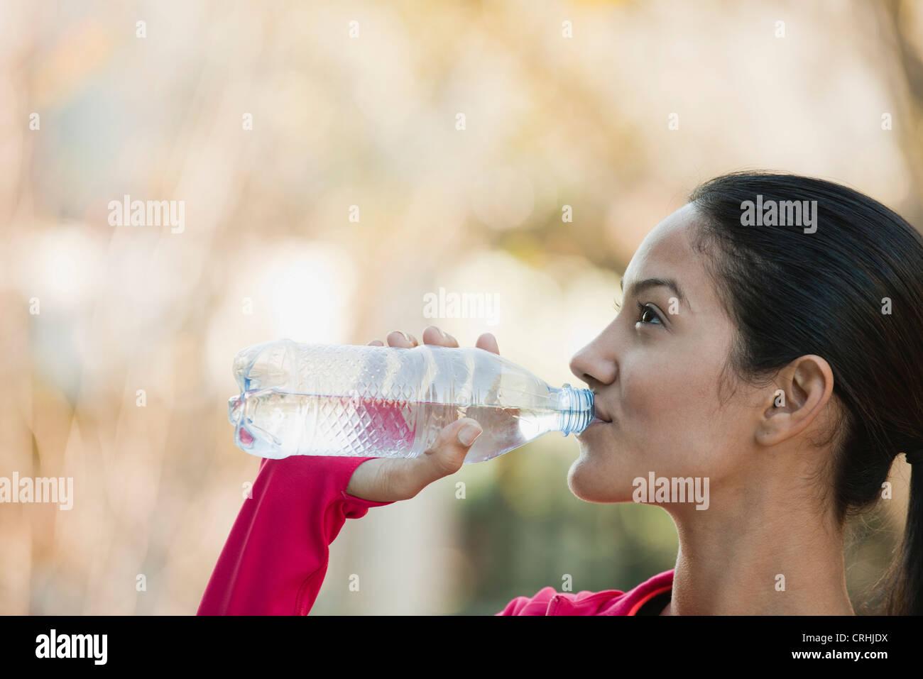 Giovane donna di bere una bottiglia di acqua minerale Immagini Stock