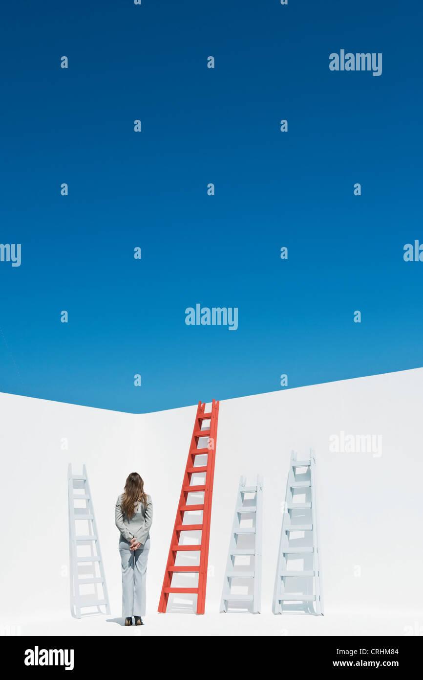 Imprenditrice contemplando le scale, vista posteriore Immagini Stock