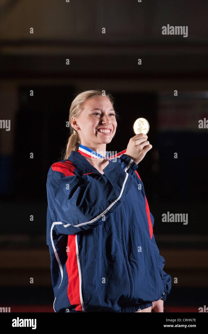 Sorridente atleta femminile tenendo la medaglia d'oro Immagini Stock