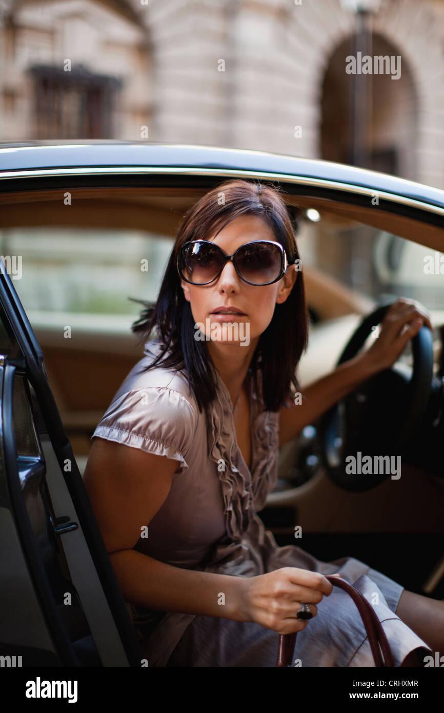 Donna del peering al di fuori della vettura Immagini Stock