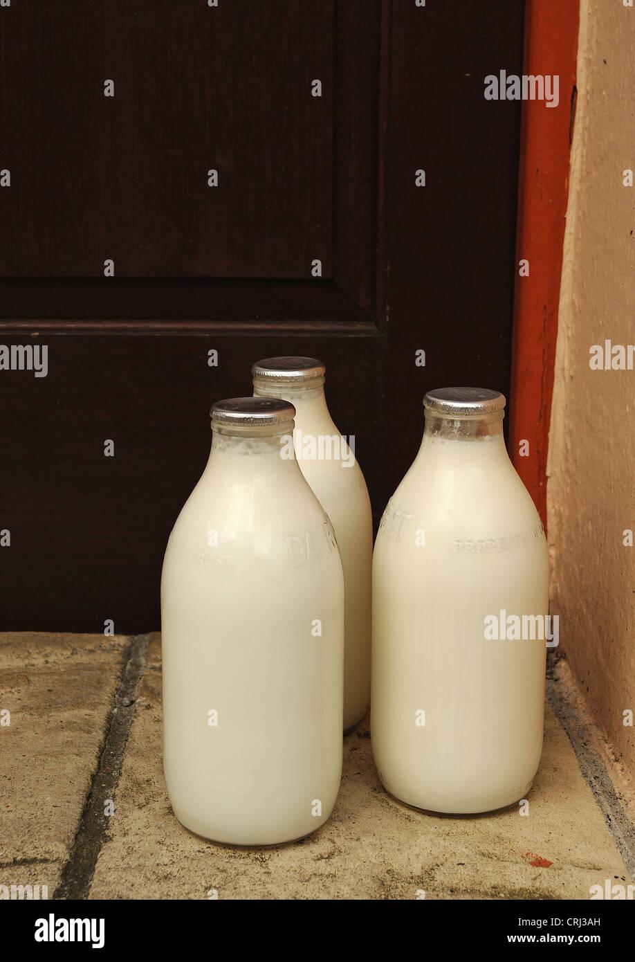 Bottiglie di latte su una porta Immagini Stock