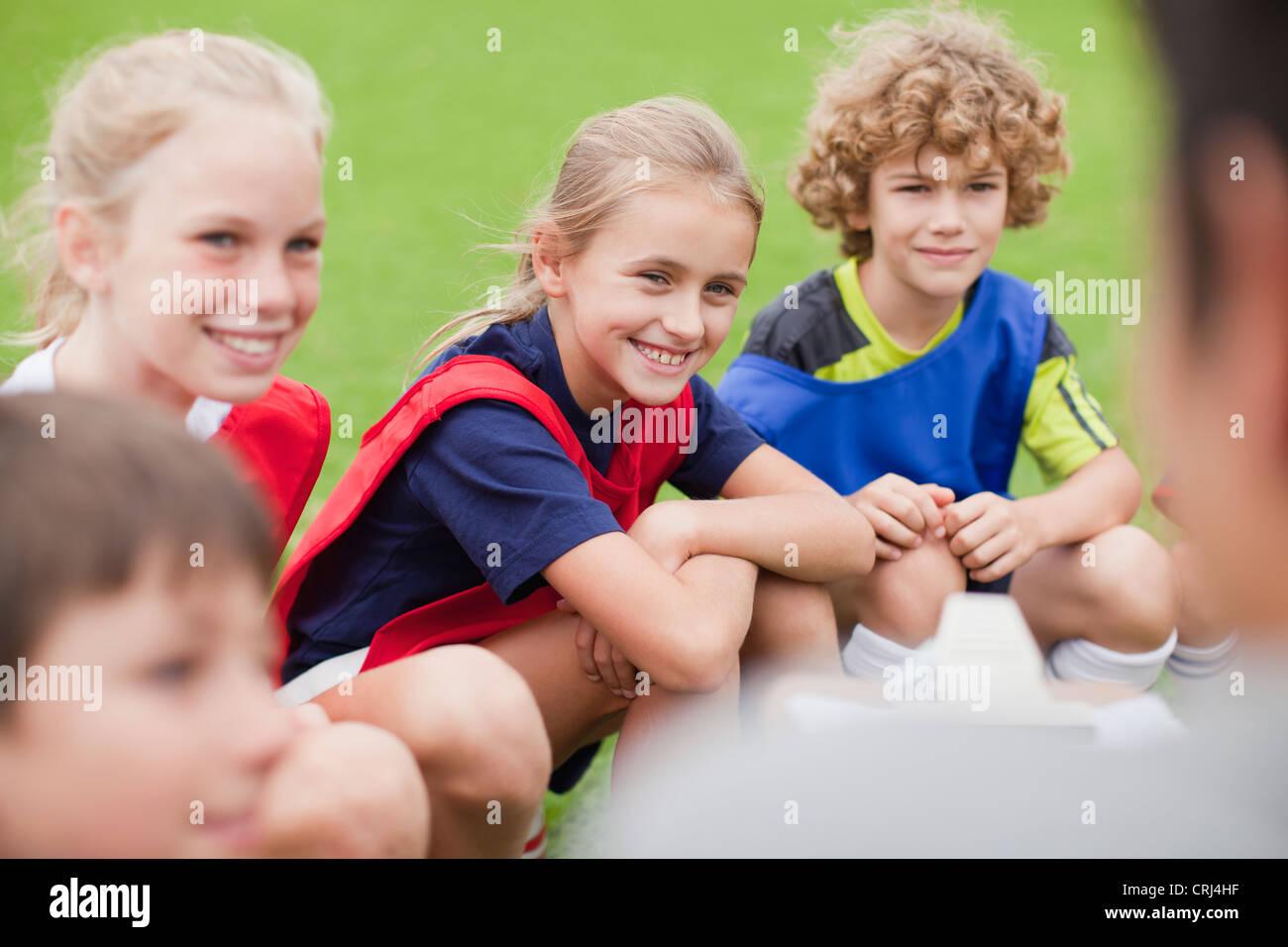 I bambini di ridere durante la pratica di calcio Immagini Stock