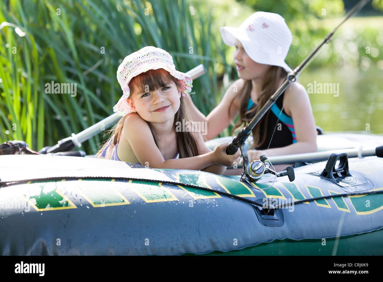 Bambine di pesca sul lago in estate Immagini Stock
