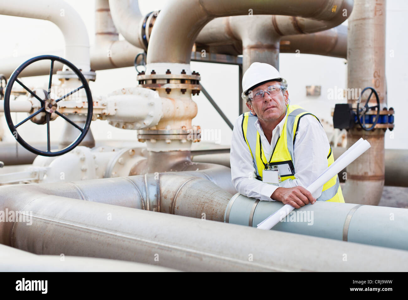 Lavoratore su tubazioni in impianti chimici Immagini Stock