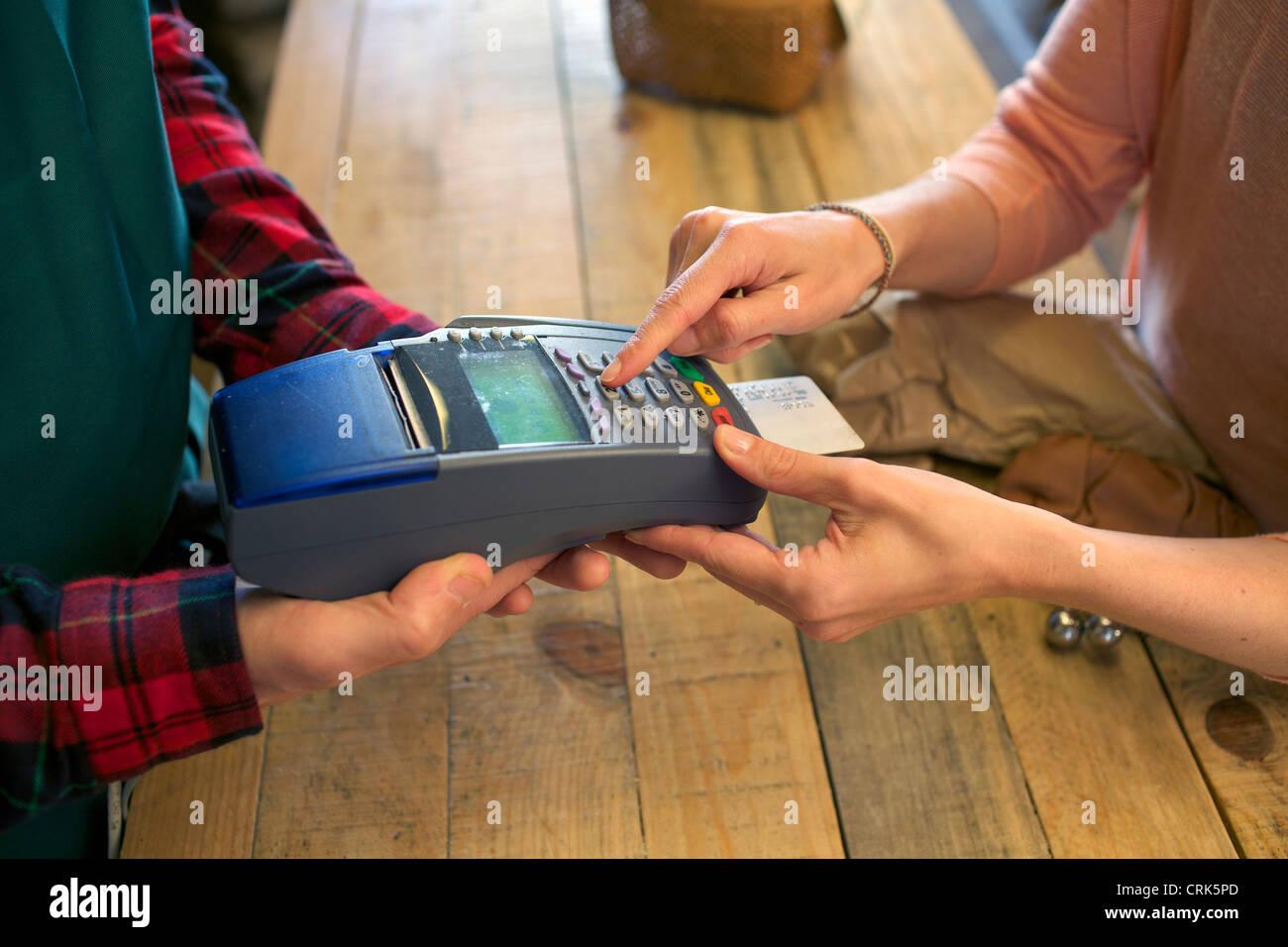 Donna fare shopping con la carta di credito in negozio Immagini Stock