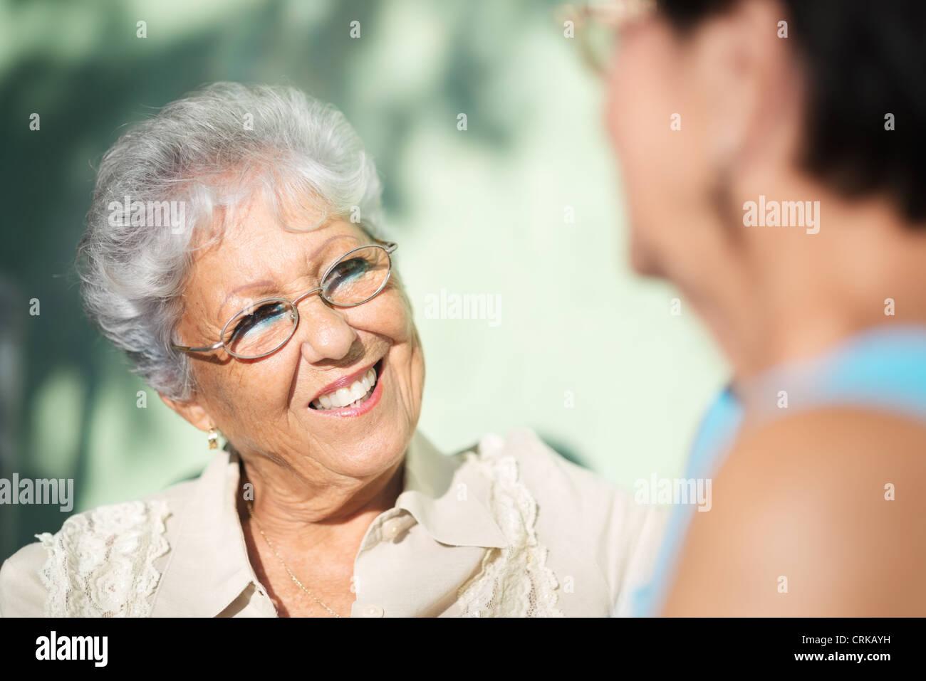 Il pensionamento attivo, due anziani amici di sesso femminile parlando sulla panchina nel parco pubblico Immagini Stock