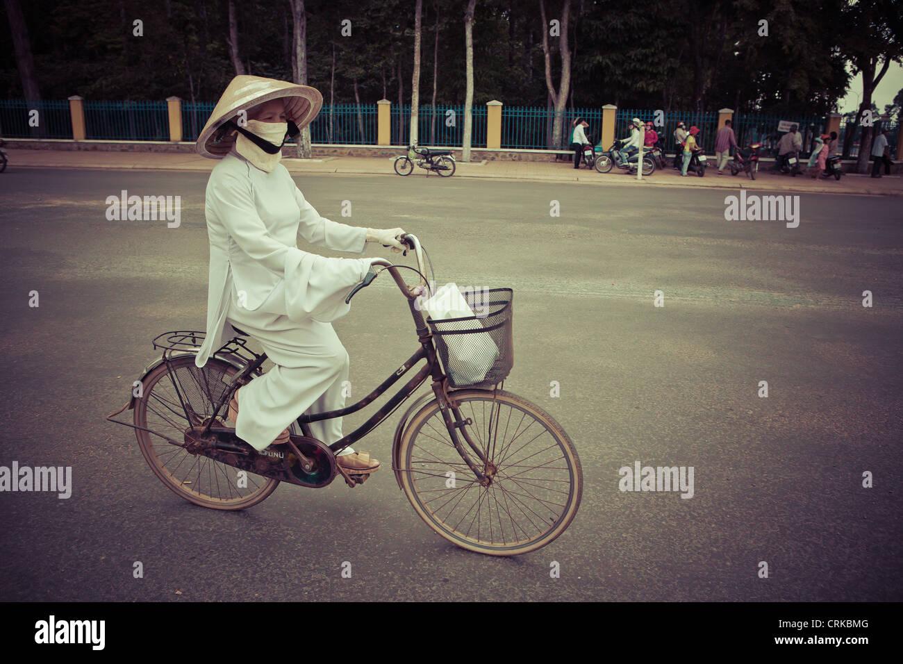 Equitazione donna la sua bicicletta nella città di Tay Ninh dopo la Cao Dai cerimonia, Vietnam Immagini Stock