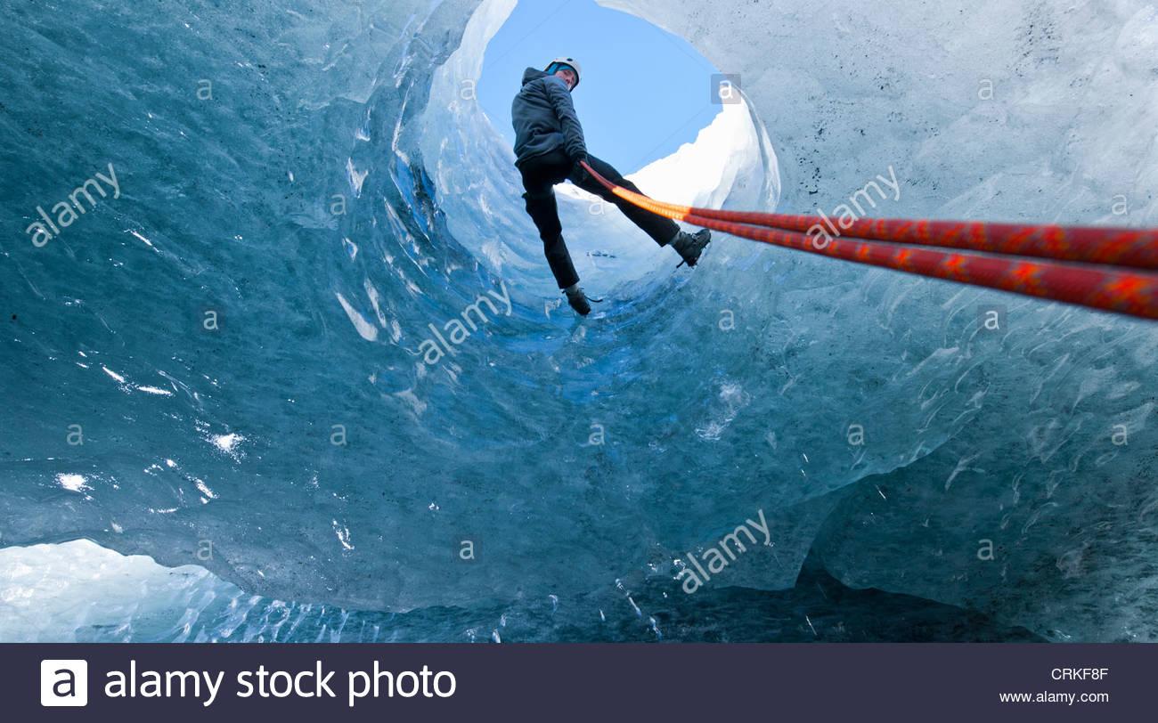 Scalatore calarsi nella caverna di ghiaccio Immagini Stock