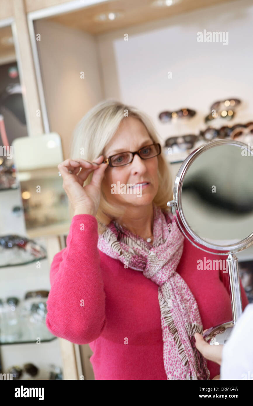 Senior donna cercando bicchieri mentre cercando in mano specchio in store Immagini Stock