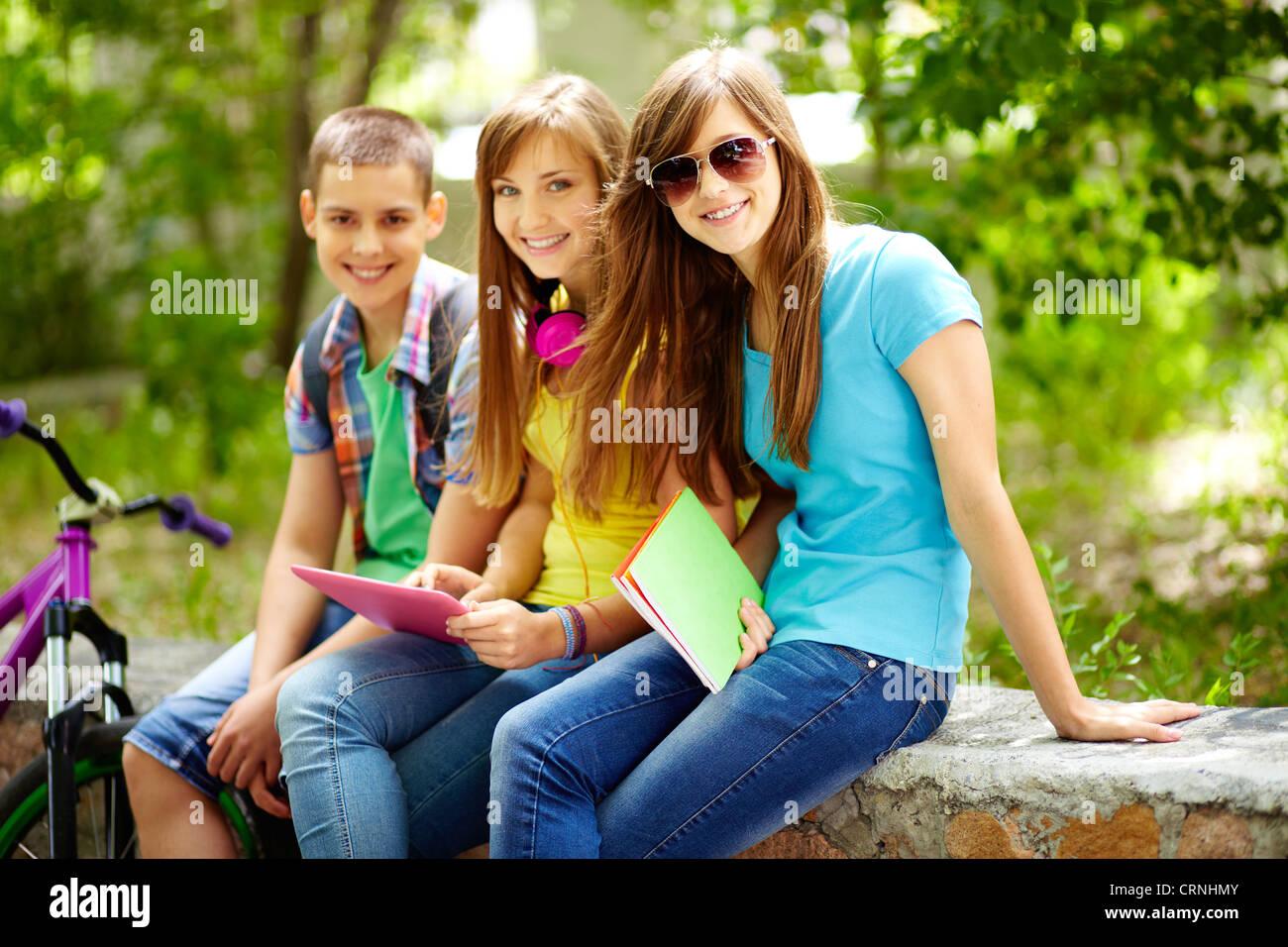 Tre amici godendo il loro tempo libero dopo le classi scolastiche Immagini Stock