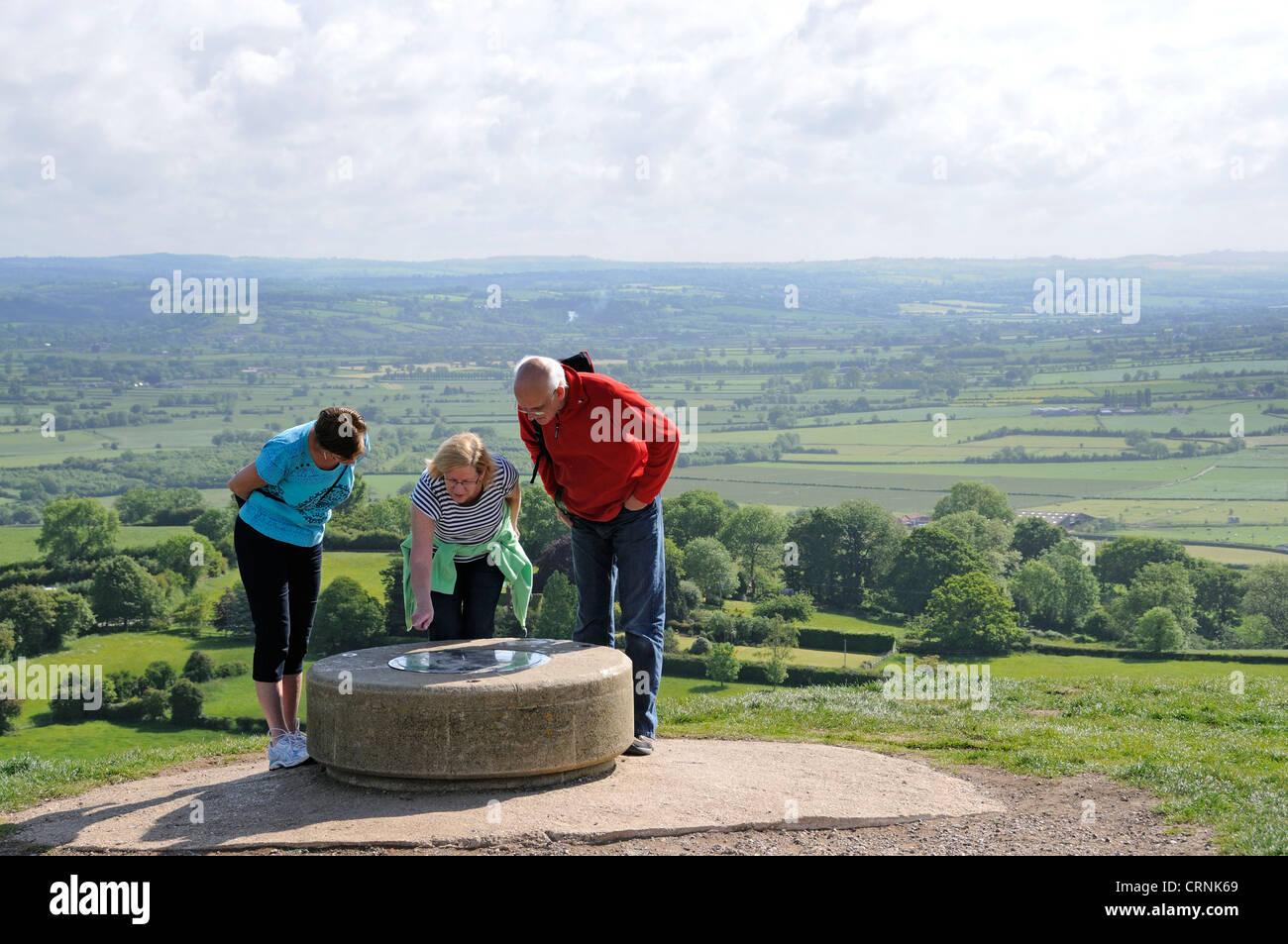 I turisti guardando il mirino mappa sul vertice di Glastonbury Tor. Immagini Stock