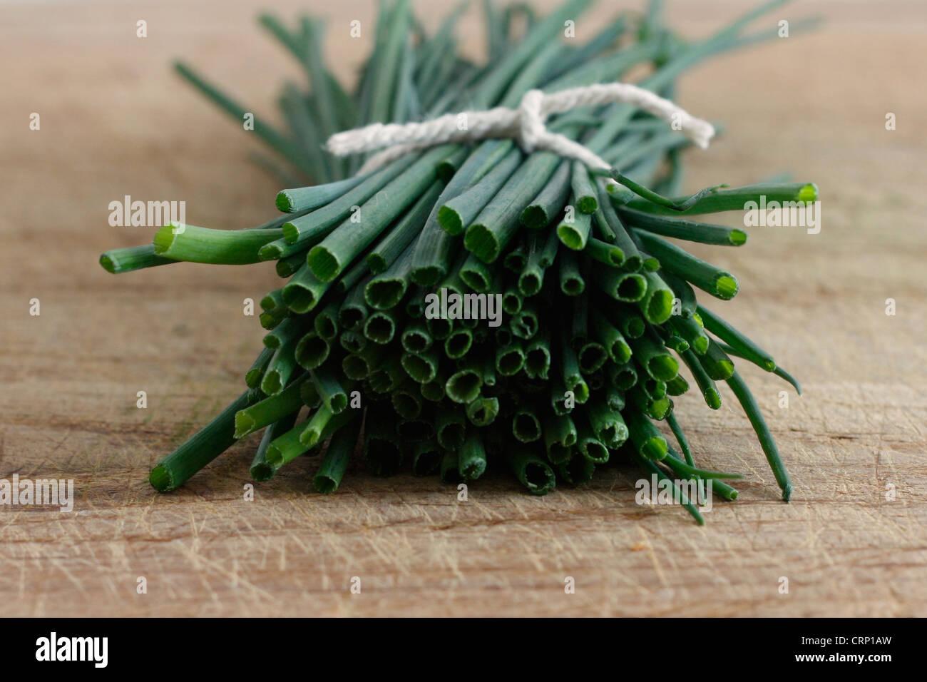Erba cipollina su una superficie in legno Immagini Stock