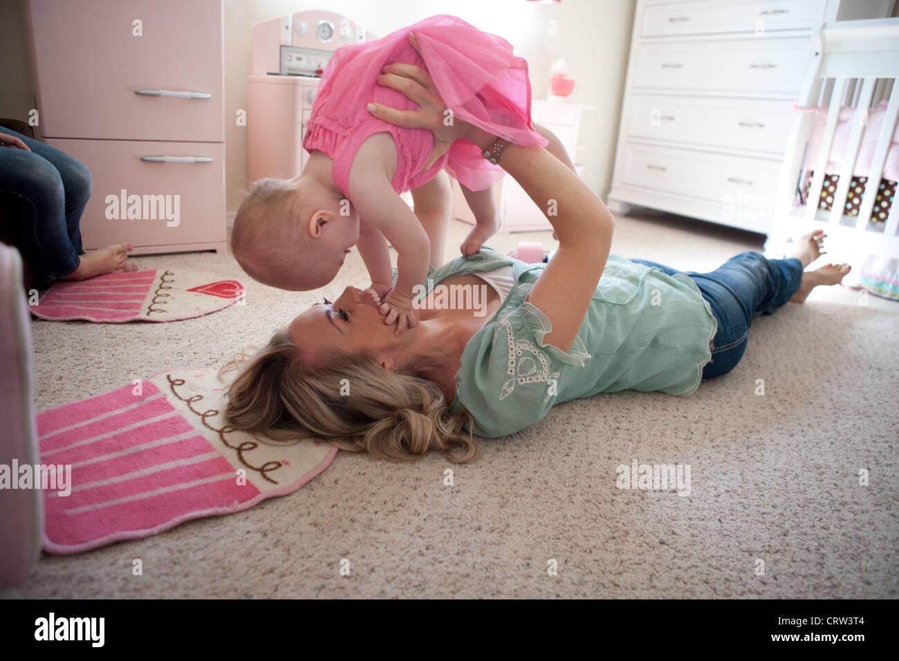 Mom tenendo le sue undici mese vecchia ragazza fino e giocando in camera da letto. Foto Stock