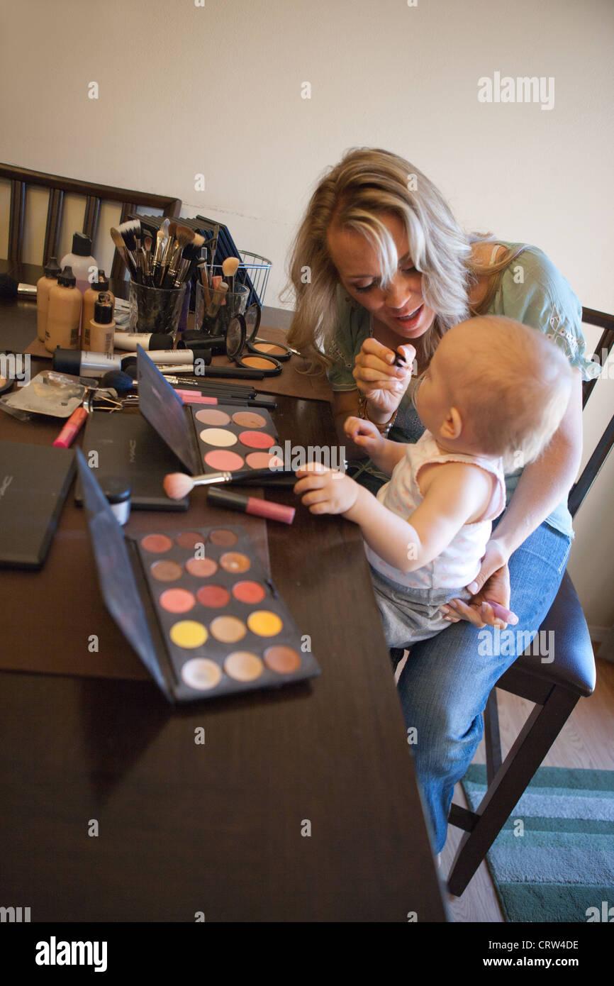 Una mamma mettendo il trucco su di lei un anno vecchio figlia a casa. Immagini Stock