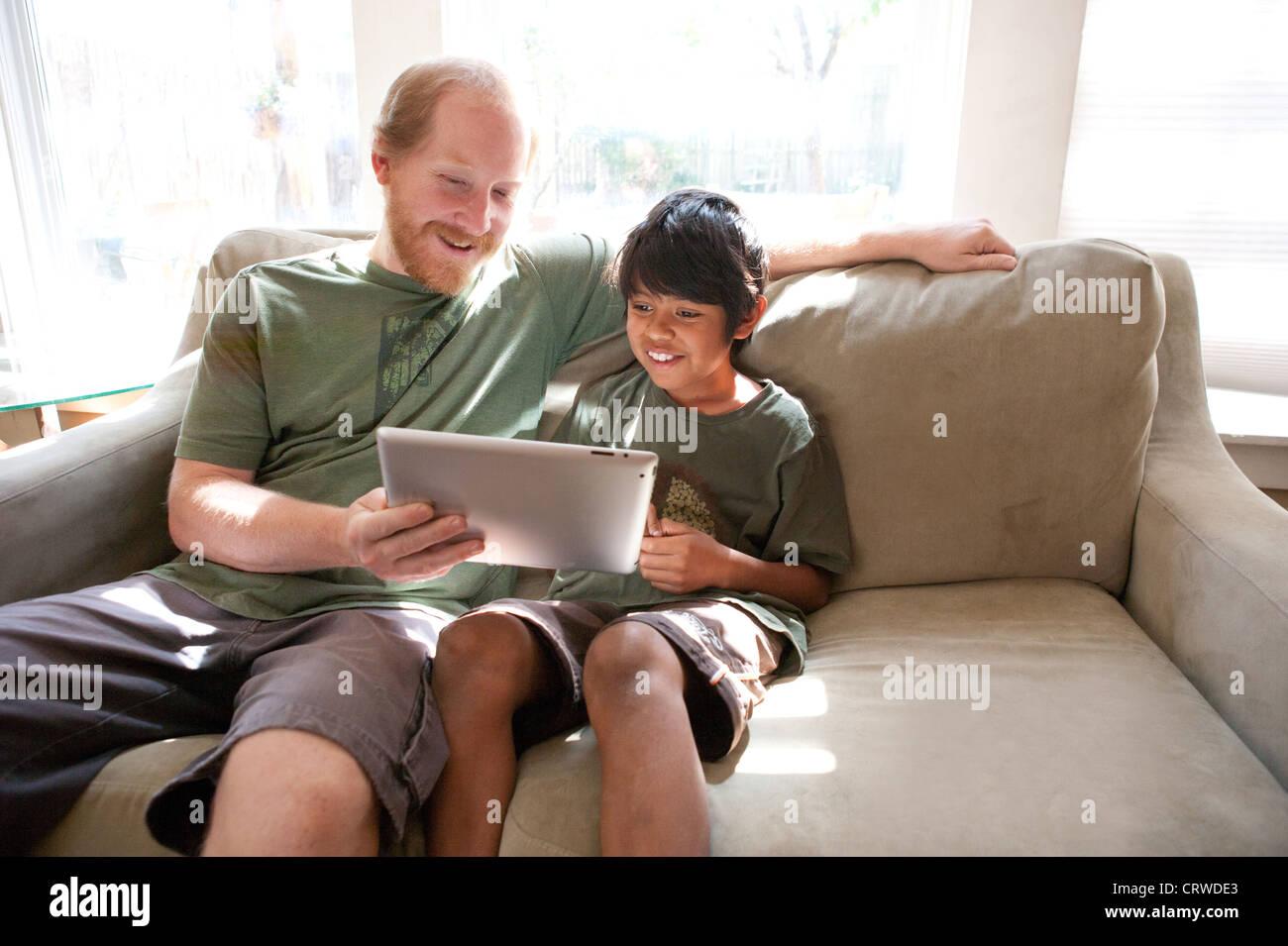 Padre e adottato dieci anni di vecchio figlio di guardare un video divertente su un Ipad a casa. Immagini Stock