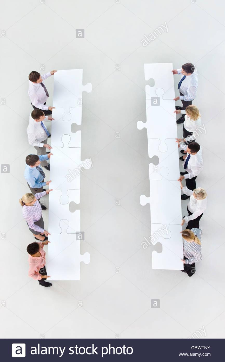 La gente di affari in piedi faccia a faccia in righe e tenere grandi pezzi di puzzle Immagini Stock