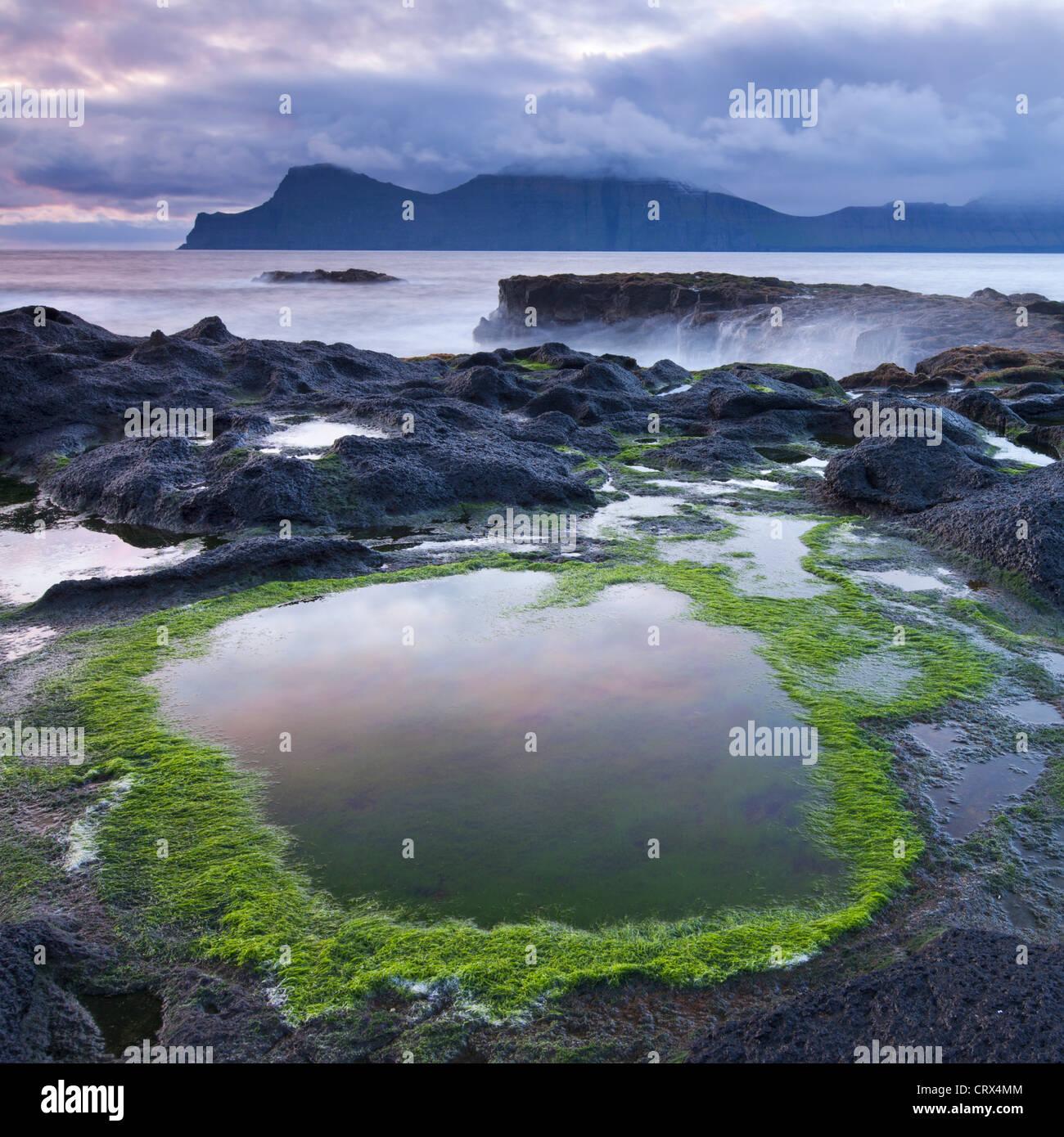 Rockpools sulle rive di Gjogv su Eysturoy, guardando verso l'isola montuosa di Kalsoy. Le isole Faerøer. Immagini Stock