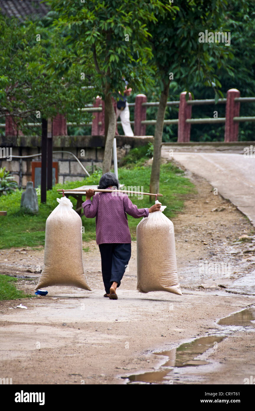 Donna cinese che trasportano carichi pesanti sulla sua spalla - Hukeng village - Hakka paese vicino a Xiamen, provincia Immagini Stock
