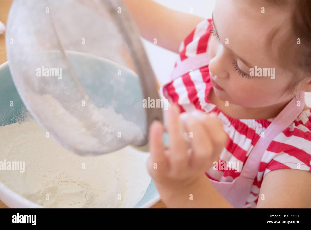 Ragazza setacciare la farina in cucina Immagini Stock