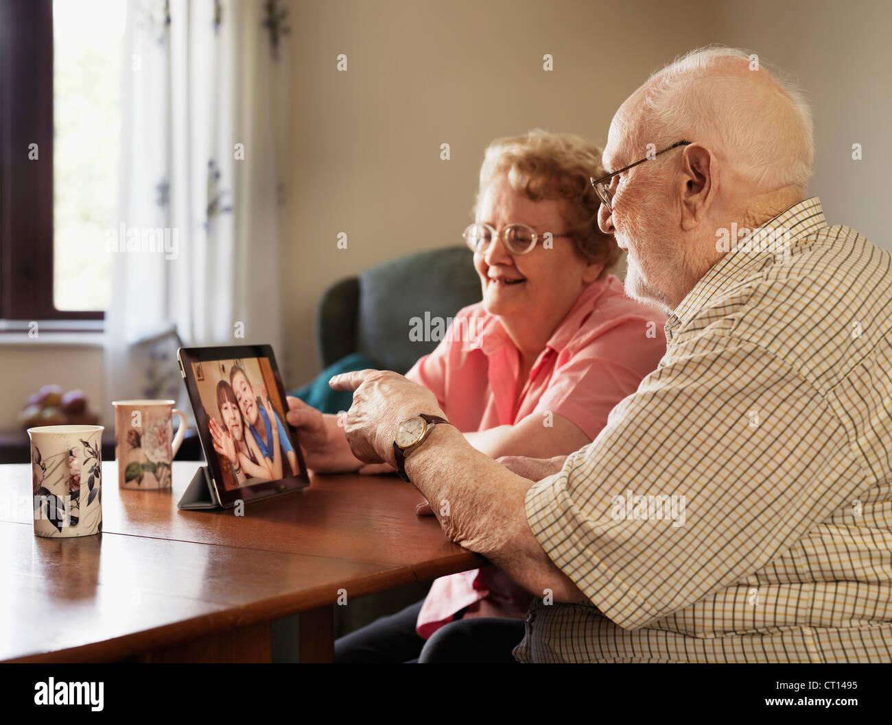 Coppia di anziani la chat video con la famiglia Immagini Stock