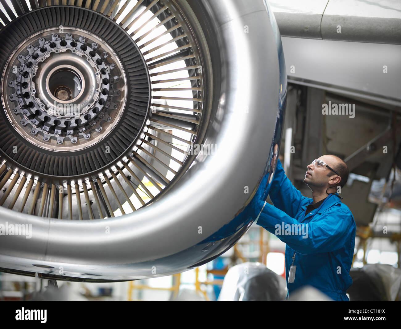 Lavoratore esaminando motore aereo Immagini Stock