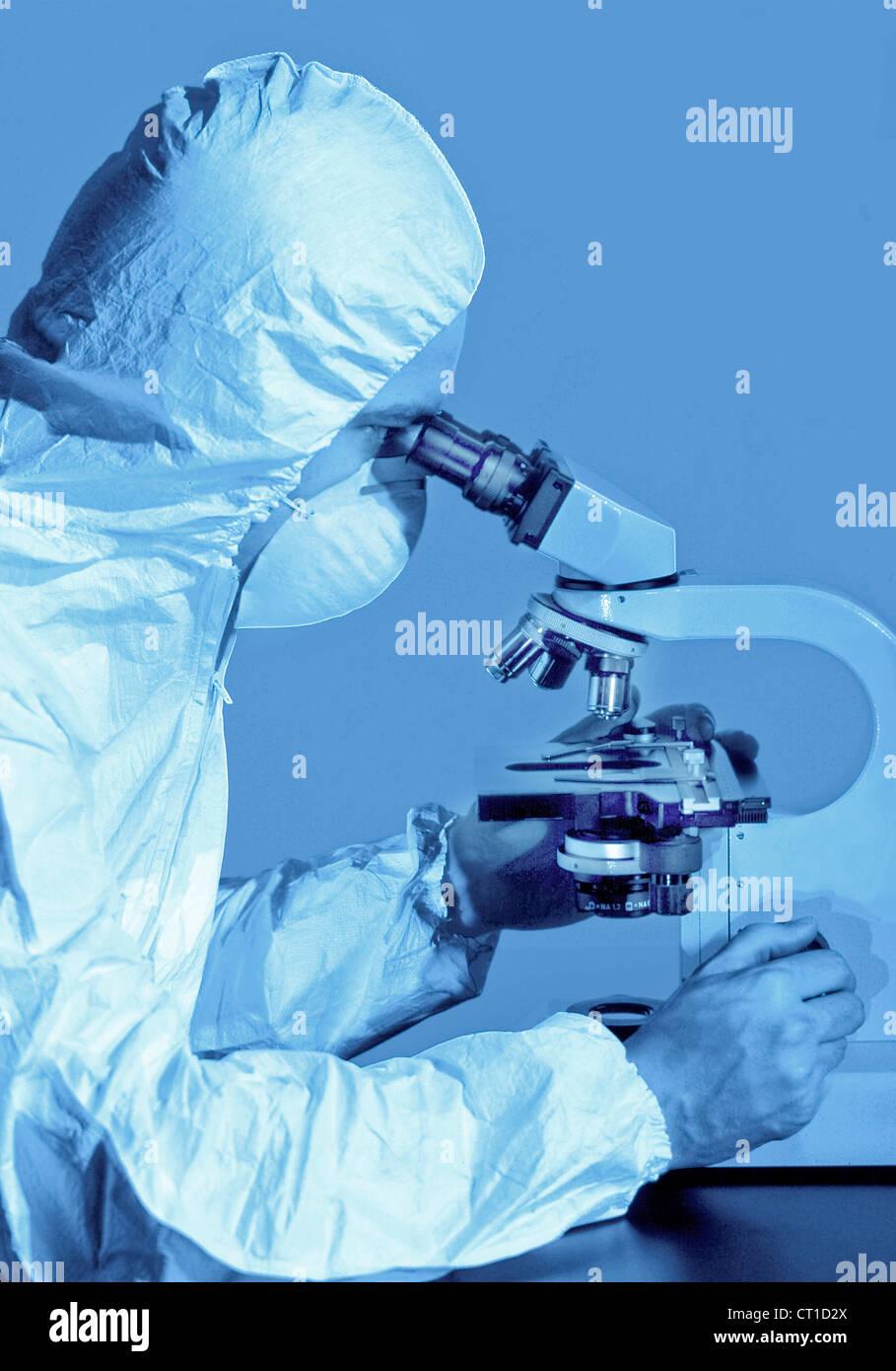 Scienziato in un microscopio Foto Stock