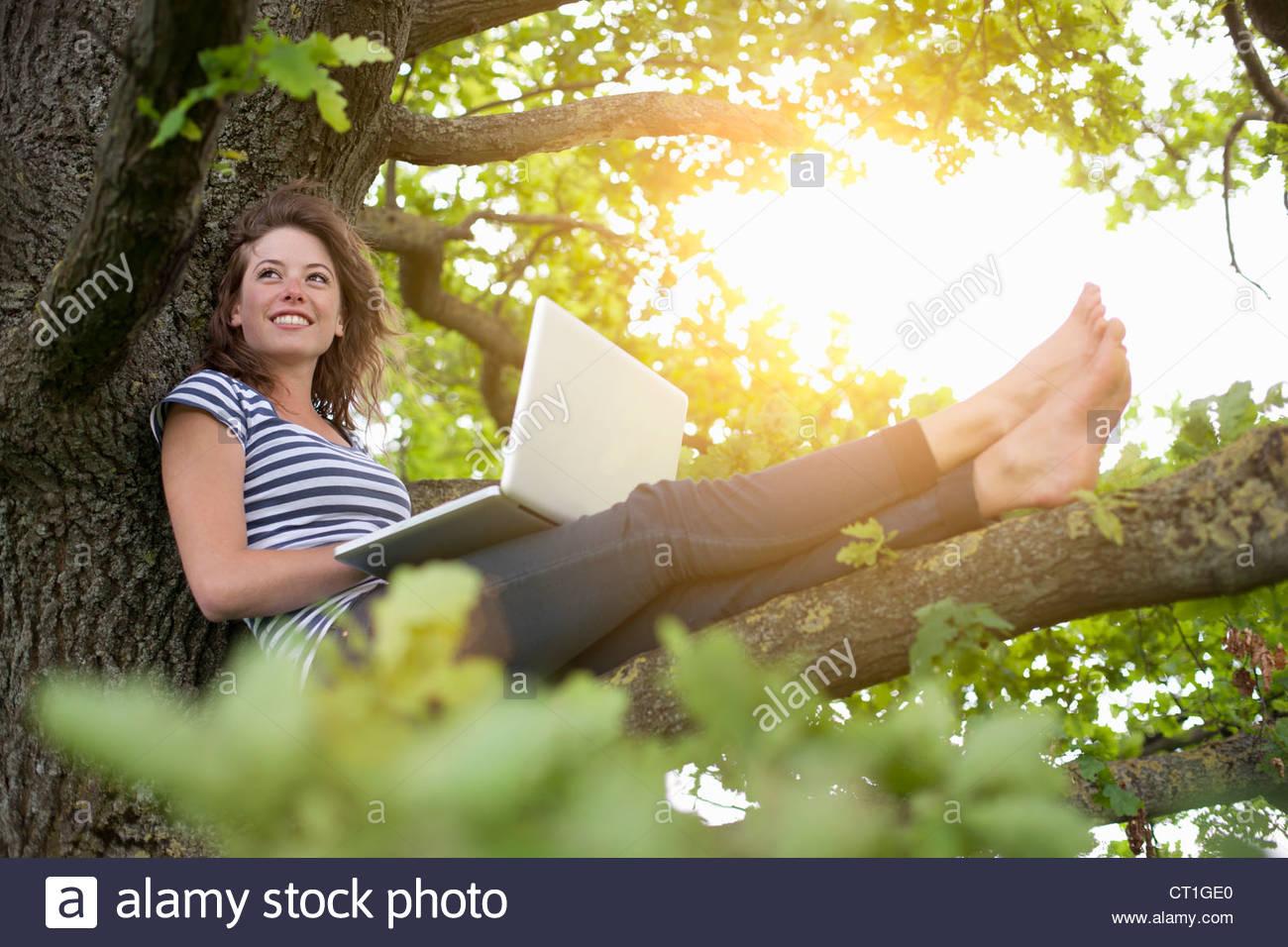 Donna sorridente con notebook nella struttura ad albero Immagini Stock